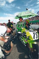 AS TSN Director of Photography Jerry Vienneau shoots, Canadian Kawasaki lead rider Owen Weichel awaits the start of the final CSBK race of 2001 at Shannonville Motorsport Park aboard the one-off works Kawasaki ZX-7RR. [Photo: Colin Fraser]