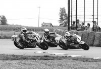 The first lap of the Formula One National at Sanair International in Quebec in 1986, and Art Robbins on his Rothmans-Honda RS500 triple (# 1) leads Steve Crevier on his ex-McMurter Pacific Yamaha FZ750 and Michel Mercier's Sunoco Suzuki GSX-R750 (# 11) through turn one.  Two hours earlier, Crevier had won his first career Pro Superbike Feature race after a great dice with local ace Mercier. [Photo: Colin Fraser]